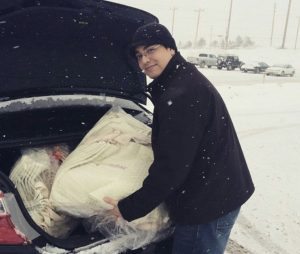 Victor Rio, founder of Expose Design LLC loading a car with marketing materials