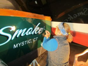 Sarah Brandon hand lettering the name Smoke on the back of a boat