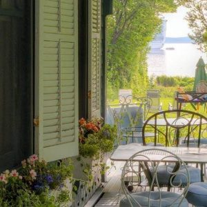 Shore Path Cottage porch view with tables and water in the distance