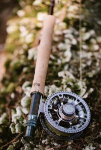 A Maine Fly Company fly-fishing reel laying on moss